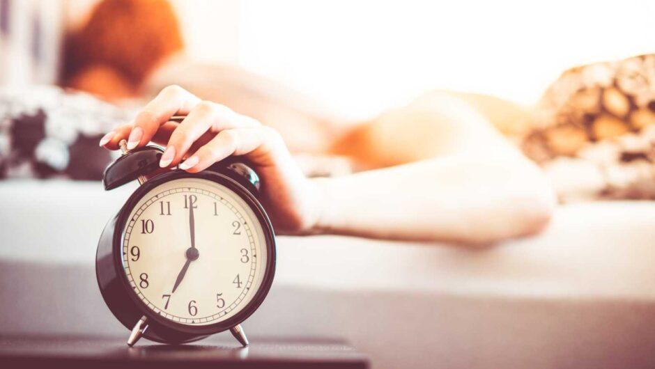 Woman Shutting Off Ringing Alarm Clock